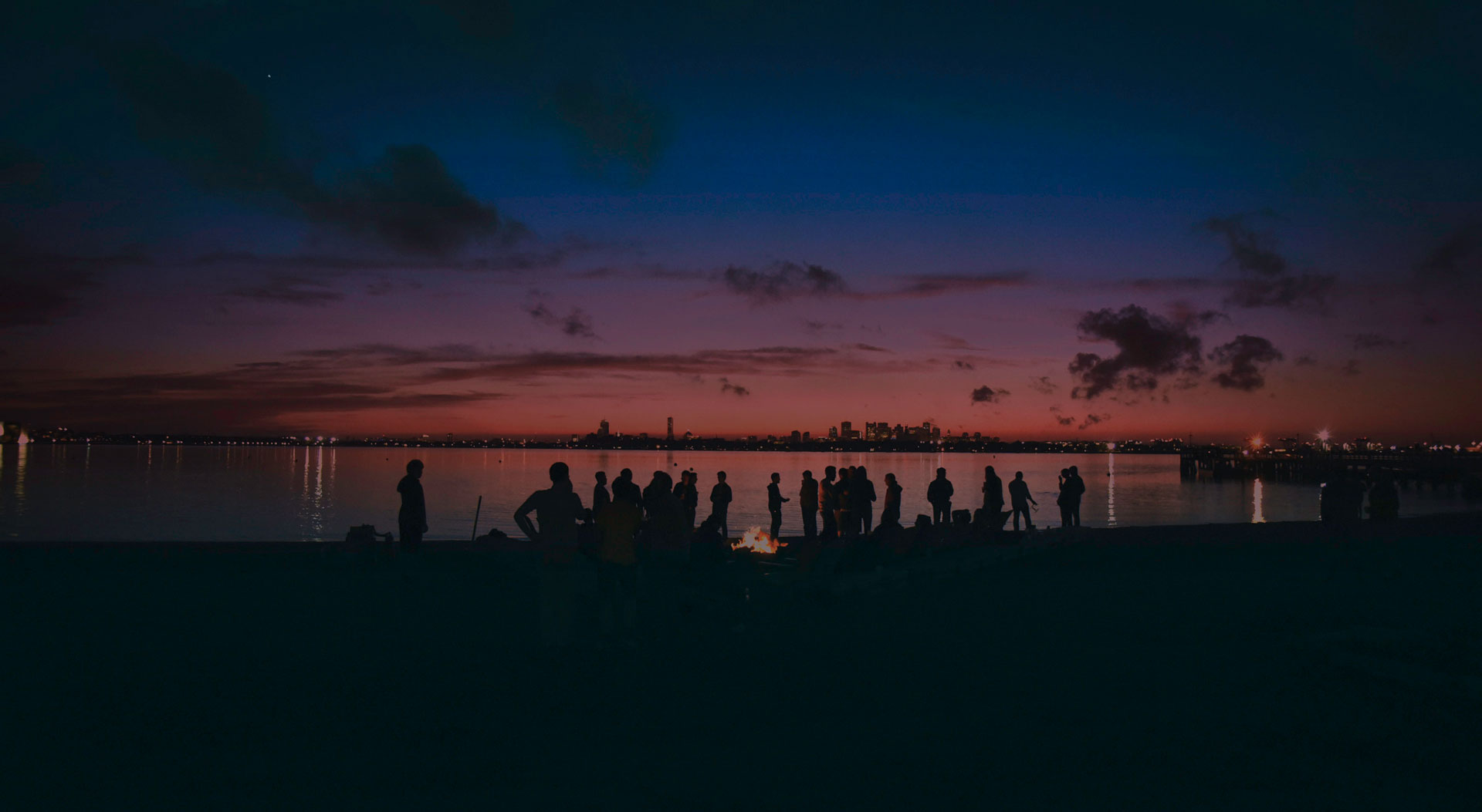 DockYard employees watching a sunset around the bonfire on an island during a company retreat.