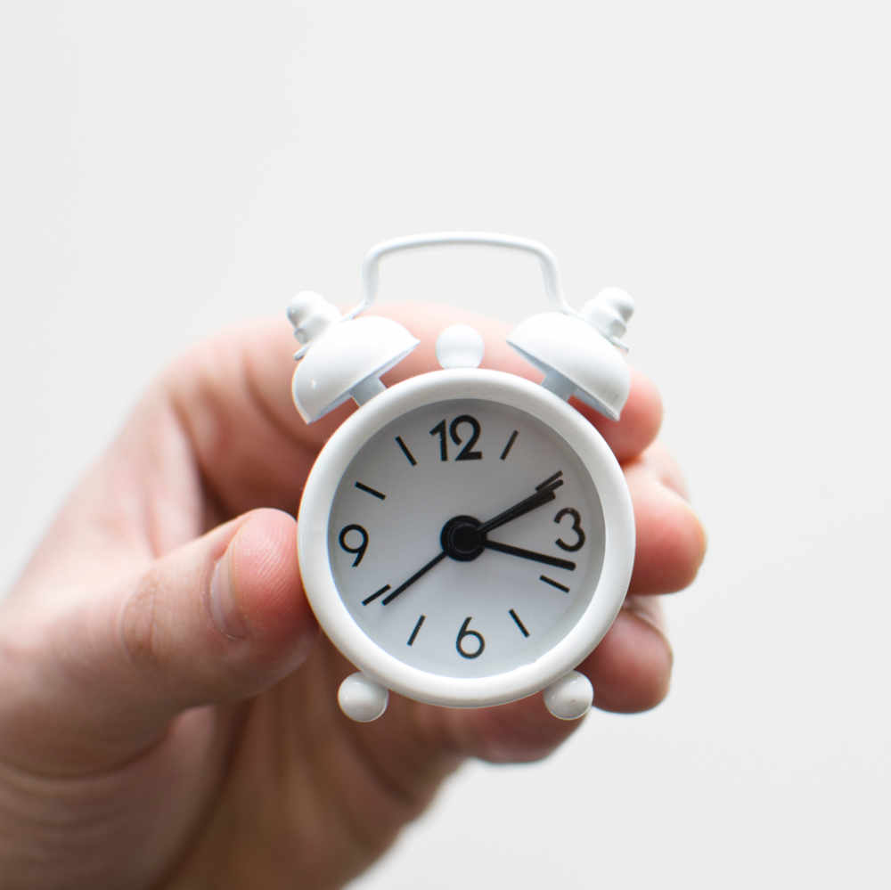 Hand holding small analog alarm clock