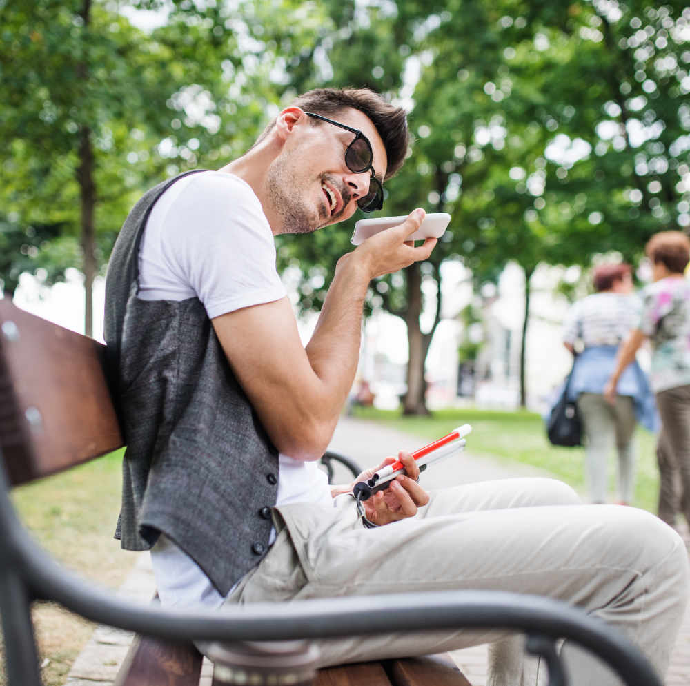 Visually impaired man sitting on bench using phone