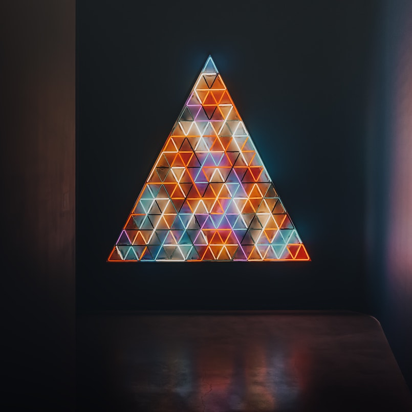 Colorful triangle made of lights with smaller triangles inside it