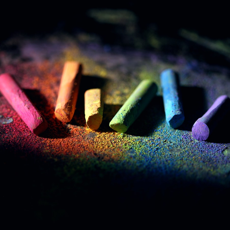 Multi colored pieces of chalk on color dusted surface