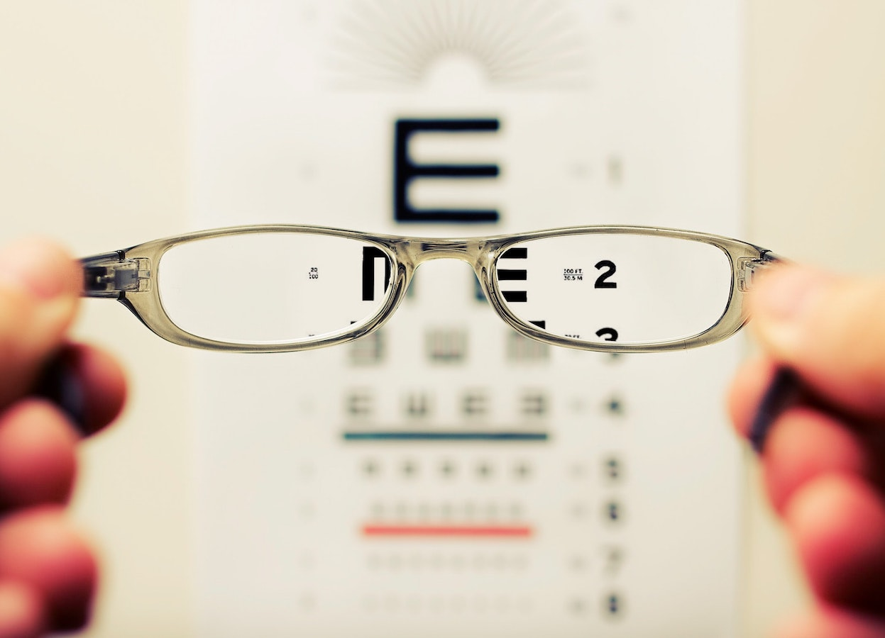 Out of focus eye test viewed through pair of glasses