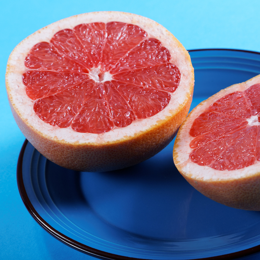 Ruby red grapefruit halfed on a blue plate.