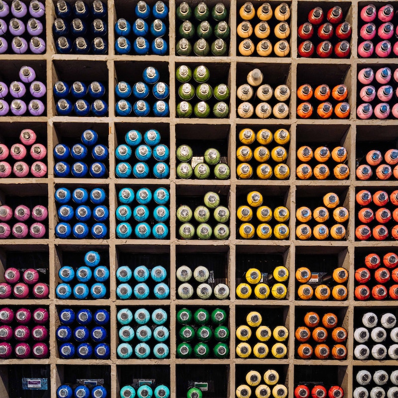 Shelves Filled with Spray Paint Bottles Organized by Color