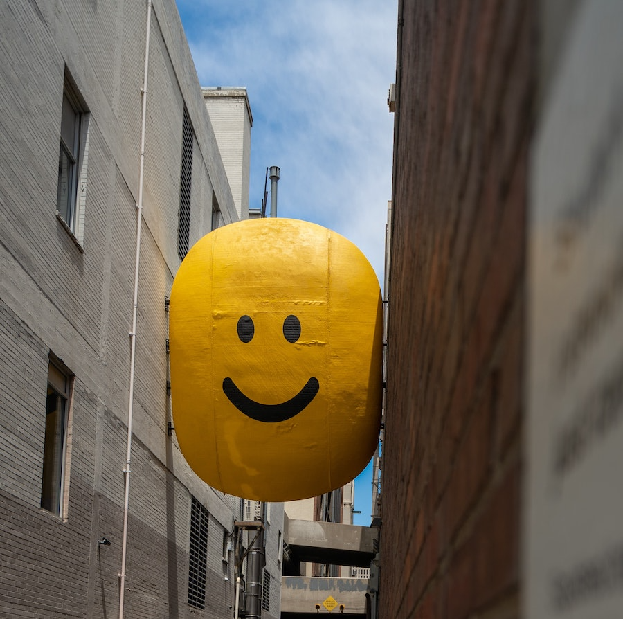 A giant smiley face balloon caught between two buildings