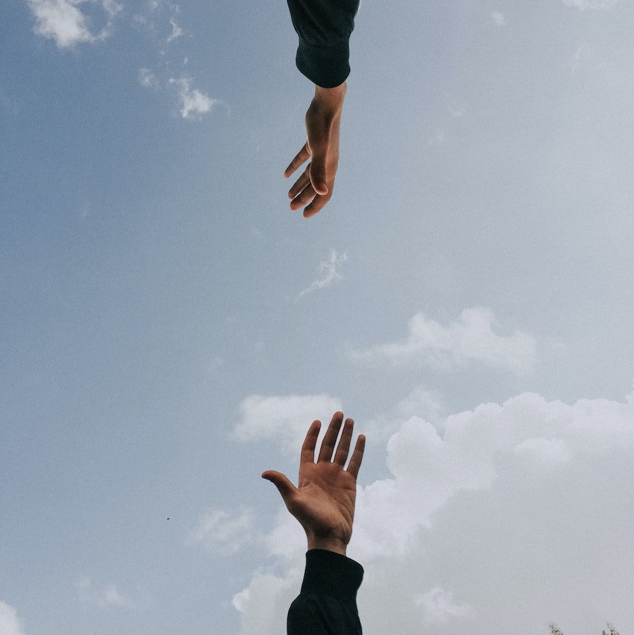 Two hands reaching out for each other across the sky